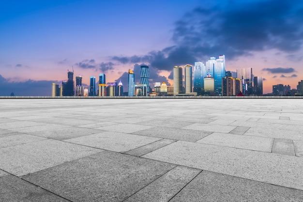 De stadswolkenkrabbers van qingdao met lege vierkante vloertegels