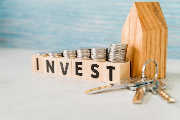 De stapel muntstukken over investeert houten blokken dichtbij het huismodel met zilveren sleutels op witte oppervlakte