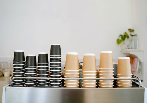 De stapel nieuwe afhaalkoffiekopjes op espressomachine in het minimale café of restaurant met kopieerruimte, eten en drinken
