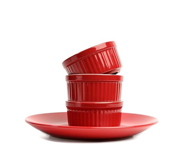 De stapel rode ceramische ronde die schotels van het cupcakebaksel op witte achtergrond worden geïsoleerd, sluit omhoog