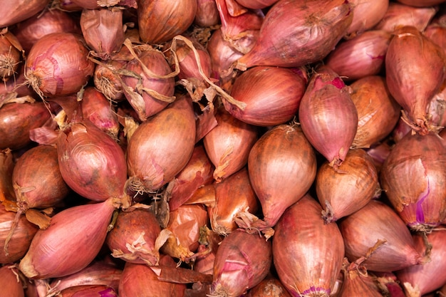 De stapel rode organische uien in schil, kan voor achtergrond worden gebruikt