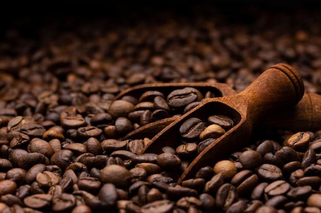 De stapel van koffiebonen met houten lepel, sluit omhoog, donkere achtergrond met exemplaarruimte