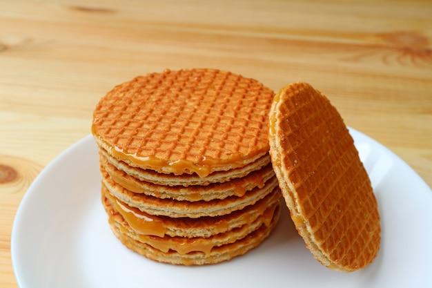 De stapel van verrukkelijke stroopwafel of karamel vulde nederlandse wafel die op witte plaat op houten lijst wordt gediend