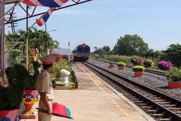 De stationsmeester staat klaar om aan te geven dat de speciale sneltrein het lokale station passeert