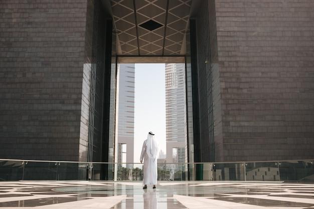 De stedelijke levensstijl van de emiraten in de grote stad met een arabische investeerder die de stad in het golfland bekijkt.