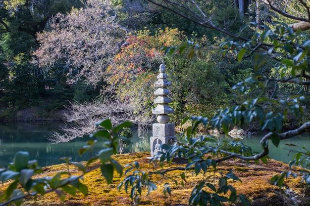 De steen boeddha bij houtsnijwerk bevindt zich in de tuin van kinkakuji tempel kyoto, japan.