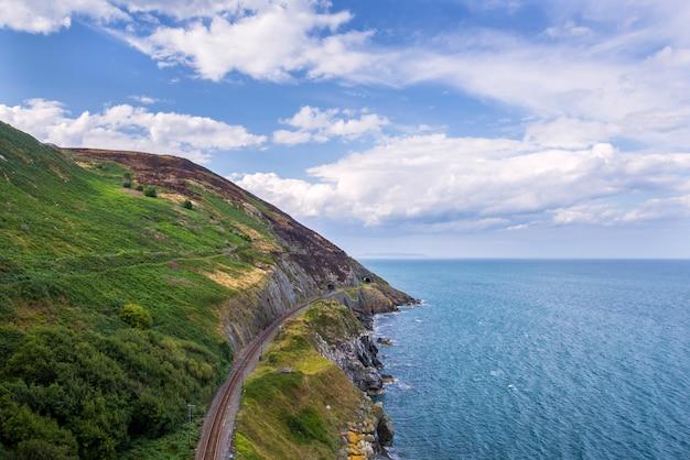 De steen schommelt bergweg en spoorweg bij ierse zeekust. bray, greystone