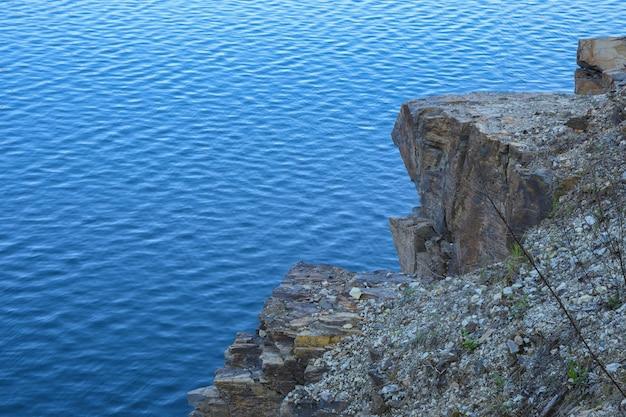 De steen schommelt dichtbij water, rivier, overzees, oceaan. blauw helder water. kunstmatige reservoirs