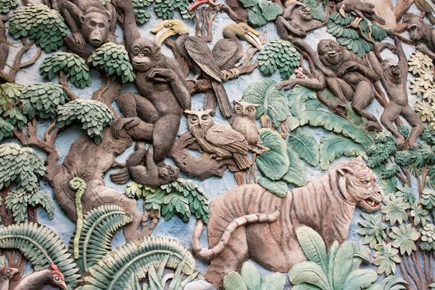 De steenbeeldhouwwerk van dieren op de muur in openbaar park