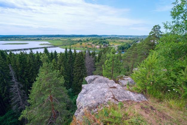 De stenen klif over het bos en de rivier