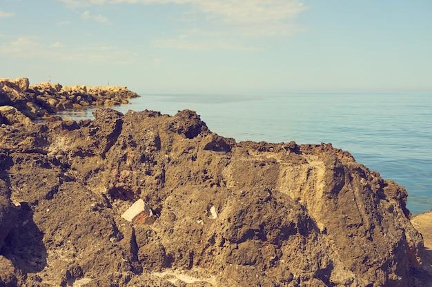 De stenen kust van de middellandse zee op een zonnige dag.