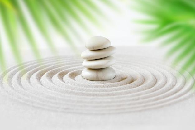 De stenen stapelen zich in het zand achter palmbladen. zen japanse tuin