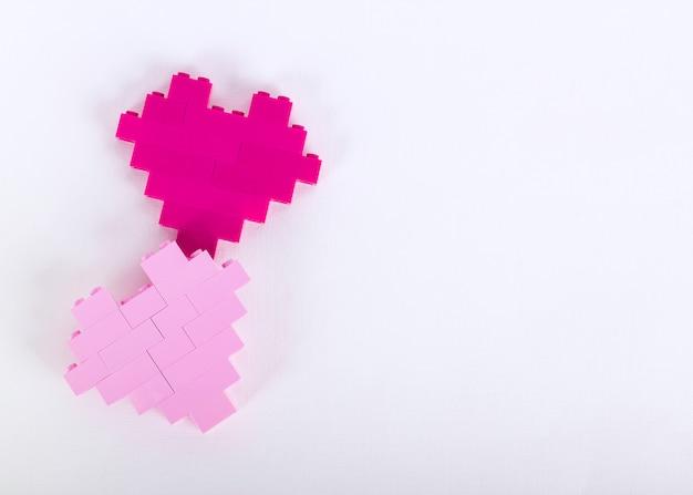 De stenen van de plastic constructor in de vorm van harten zijn rood, magenta, roze. witte achtergrond.