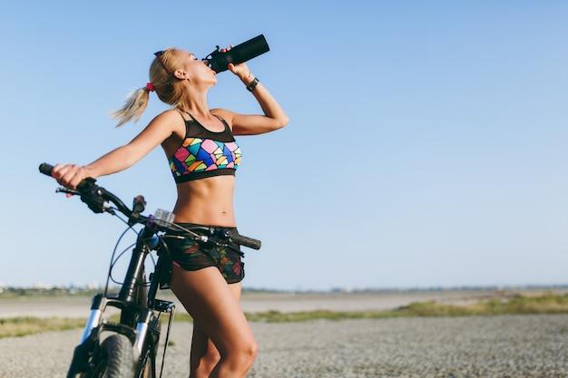 De sterke blonde vrouw in een kleurrijk pak en zonnebril staat in de buurt van een fiets, drinkt water uit een zwarte fles in een woestijngebied. geschiktheidsconcept.