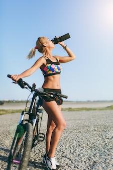De sterke blonde vrouw in een kleurrijk pak en zonnebril staat in de buurt van een fiets, drinkt water uit een zwarte fles in een woestijngebied. geschiktheidsconcept. Gratis Foto