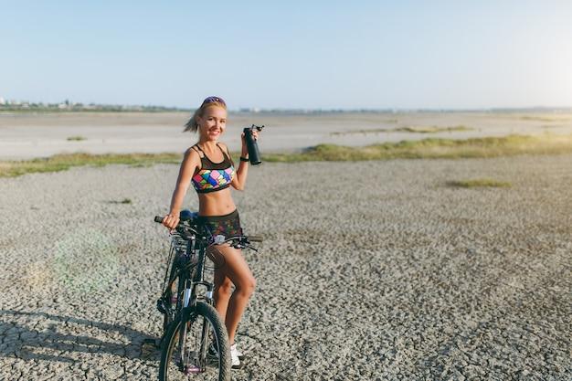 De sterke blonde vrouw in een kleurrijk pak en zonnebril staat in de buurt van een fiets met zwarte fles water in een woestijngebied. geschiktheidsconcept.