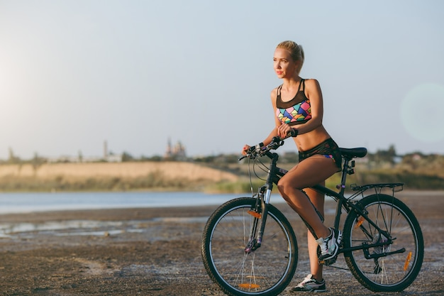 De sterke blonde vrouw in een kleurrijk pak zit op een fiets in een woestijngebied bij het water en kijkt naar de zon. geschiktheidsconcept.