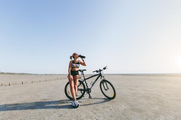 De sterke blonde vrouw in een veelkleurig pak en zonnebril staat in de buurt van een fiets, drinkt water uit een fles in een woestijngebied en kijkt naar de zon. geschiktheidsconcept.