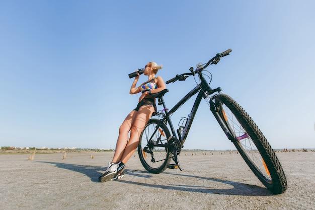 De sterke blonde vrouw in een veelkleurig pak en zonnebril staat in de buurt van een fiets, drinkt water uit een fles in een woestijngebied. geschiktheidsconcept.