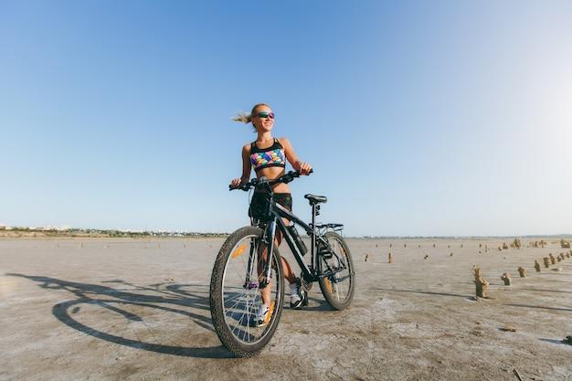 De sterke blonde vrouw in een veelkleurig pak en zonnebril staat in de buurt van een fiets in een woestijngebied en kijkt naar de zon. geschiktheidsconcept.