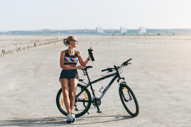 De sterke blonde vrouw in een veelkleurig pak en zonnebril staat in de buurt van een fiets met zwarte fles water in een woestijngebied en kijkt naar de zon. geschiktheidsconcept.