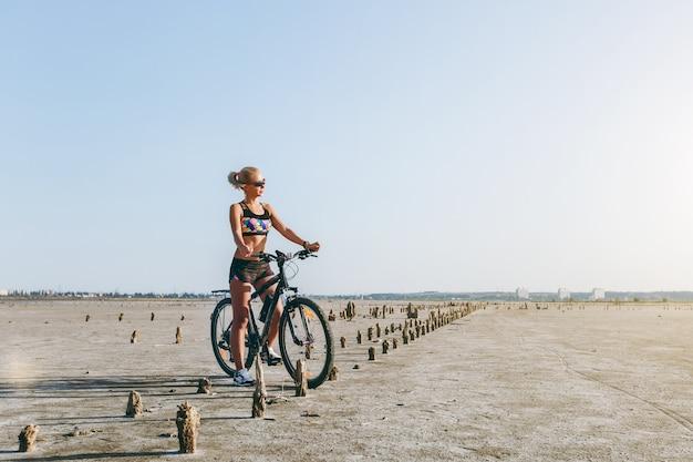 De sterke blonde vrouw in een veelkleurig pak en zonnebril zit op een fiets in een woestijngebied en kijkt naar de zon. geschiktheidsconcept.