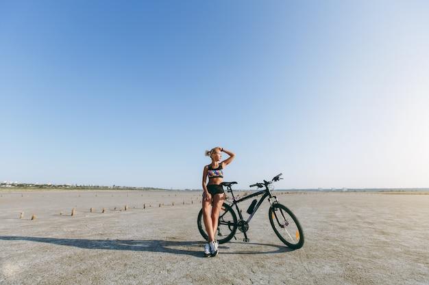 De sterke blonde vrouw in een veelkleurig pak staat bij een fiets in een woestijngebied en kijkt naar de zon. geschiktheidsconcept.