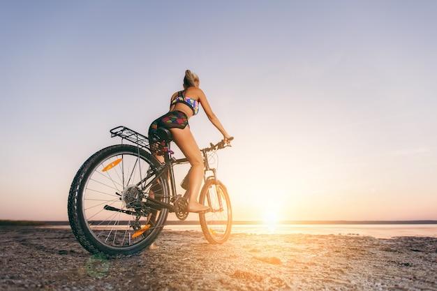 De sterke blonde vrouw in een veelkleurig pak zit op een fiets in een woestijngebied bij het water en kijkt naar de zon. geschiktheidsconcept. achteraanzicht