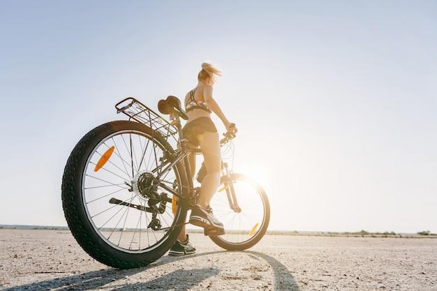 De sterke blonde vrouw in een veelkleurig pak zit op een fiets in een woestijngebied en kijkt naar de zon. geschiktheidsconcept. achteraanzicht. detailopname