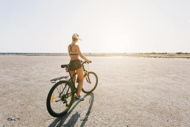 De sterke blonde vrouw in een veelkleurig pak zit op een fiets in een woestijngebied en kijkt naar de zon. geschiktheidsconcept. achteraanzicht