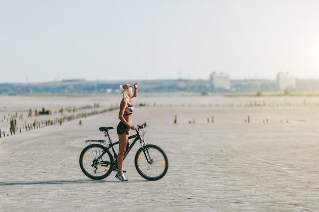 De sterke blonde vrouw in een veelkleurig pak zit op een fiets in een woestijngebied en kijkt naar de zon. geschiktheidsconcept.