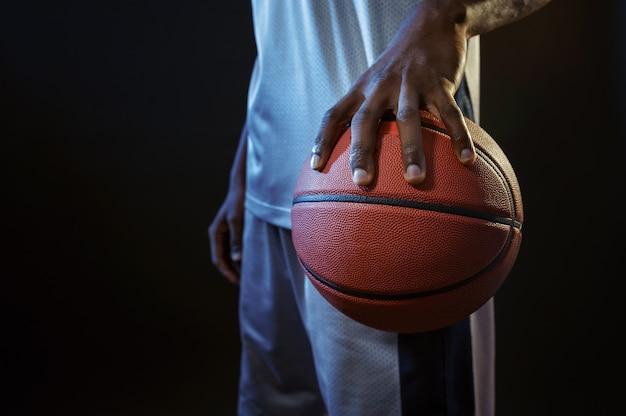 De sterke hand van de basketbalspeler houdt bal in studio, zwarte achtergrond. professionele mannelijke baller in sportkleding die sportspel speelt, lange sportman