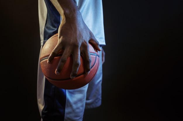 De sterke hand van de basketbalspeler houdt de bal vast. professionele mannelijke baller in sportkleding die sportspel speelt, lange sportman