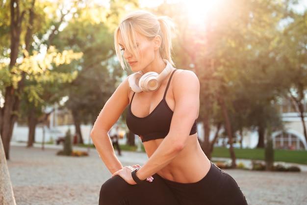 De sterke jonge sportenvrouw maakt sporten uitrekkende oefeningen.