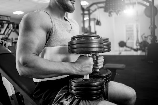 De sterke mensenbodybuilder zit met zware domoren op de gymnastiek. gespierd lichaam van een sportman in het sportcentrum. zwart / wit foto.