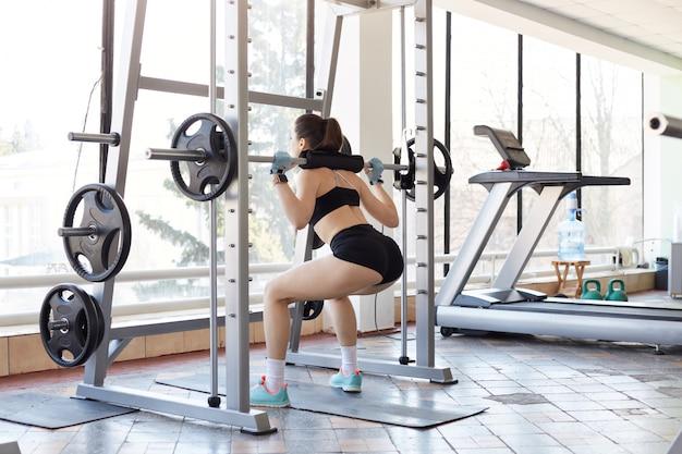De sterke, stoere sportvrouw steunt squats uit het raam en ontwikkelt haar spieren. de jonge zwarte haired dame draagt zwart strak sportkostuum. mensen en een gezonde levensstijl.