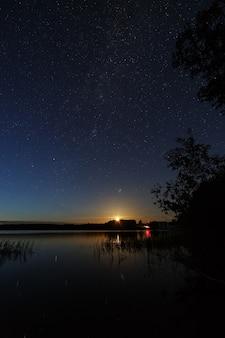 De sterren aan de nachtelijke hemel boven de rivier.