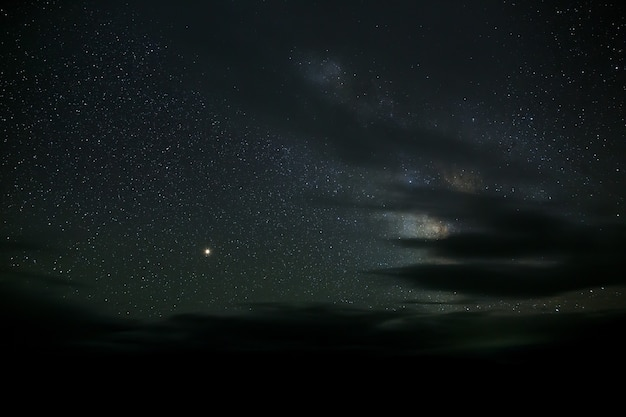 De sterren van de melkweg 's nachts aan de hemel gloeien door de wolken