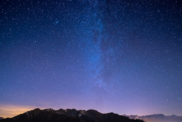 De sterrenhemel in de kersttijd en de majestueuze hoge bergketen van de italiaanse franse alpen