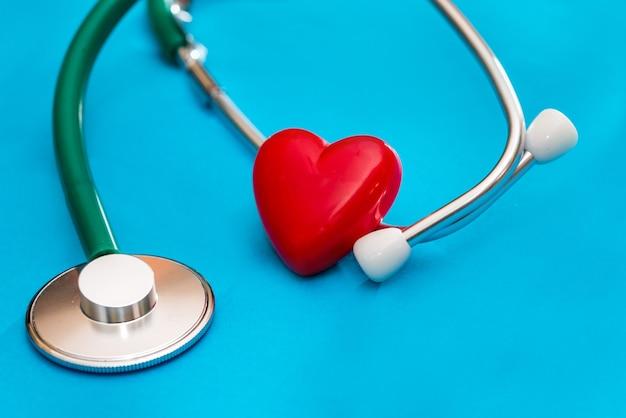 De stethoscoop en het hart zijn geïsoleerd op een blauwe achtergrond