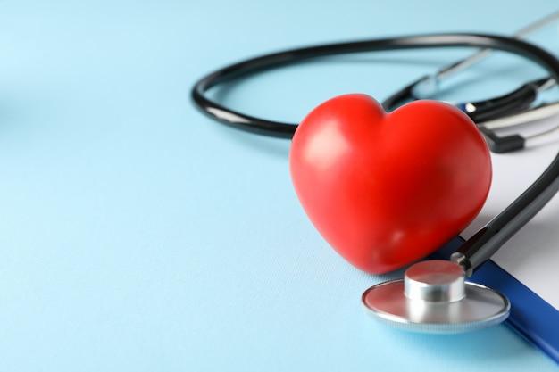 De stethoscoop en het rode hart op blauwe achtergrond, sluiten omhoog. gezondheidszorg