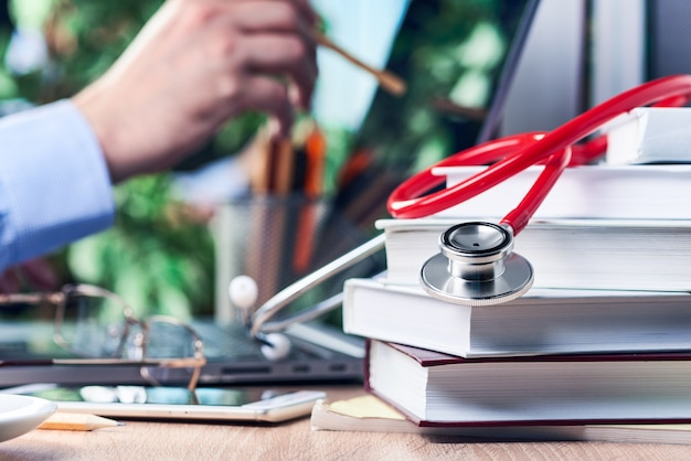 De stethoscoop ligt op medische boeken. een mannenhand houdt een potlood vast en wijst het naar het laptopscherm