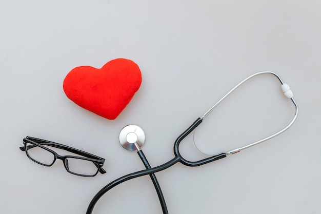 De stethoscoopglazen van het geneeskundemateriaal en rood die hart op witte achtergrond wordt geïsoleerd