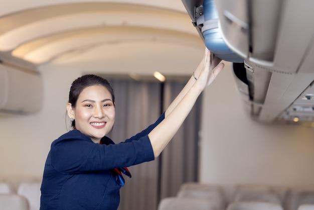 De stewardess helpt de passagiers om hun bagage in de cabine van het vliegtuig te zetten. stewardess in het vliegtuig. Premium Foto