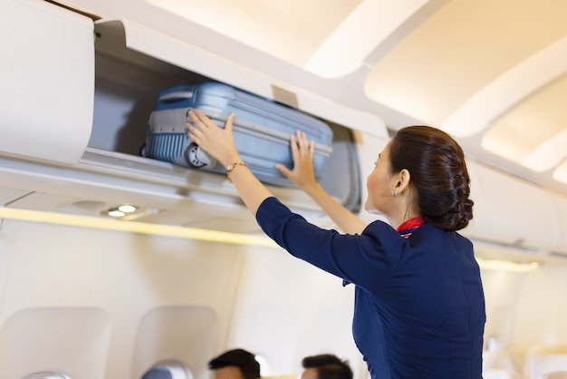De stewardess helpt de passagiers om hun bagage in de cabine van het vliegtuig te zetten. stewardess in het vliegtuig.