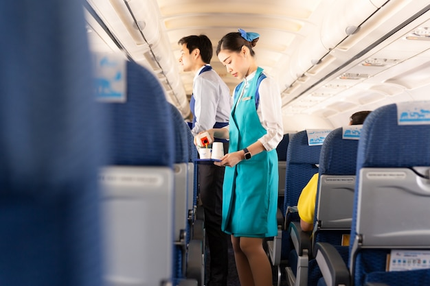 De stewardess van bangkok airways serveert voedsel aan passagiers aan boord.
