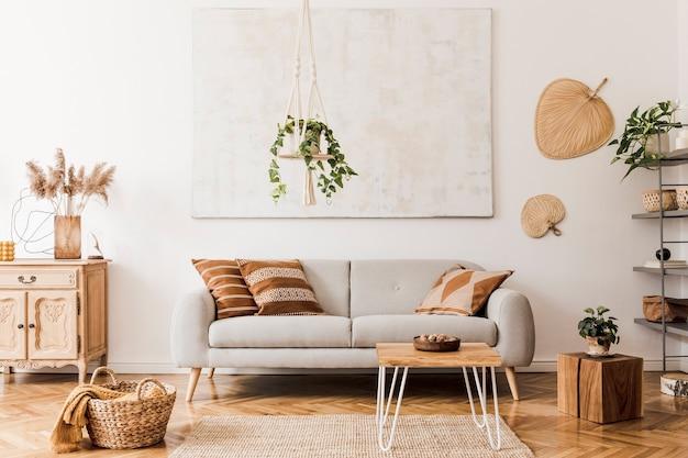 De stijlvolle boho-compositie in het woonkamerinterieur met grijze designbank, houten salontafelkast en elegante persoonlijke accessoires