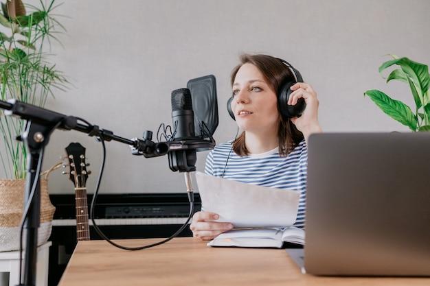 De stijlvolle en goed opgeleide blanke vrouw neemt podcasts op in een opnamestudio of bij haar thuis