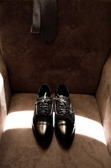 De stijlvolle schoenen van de bruidegom liggen op een zachte fauteuil