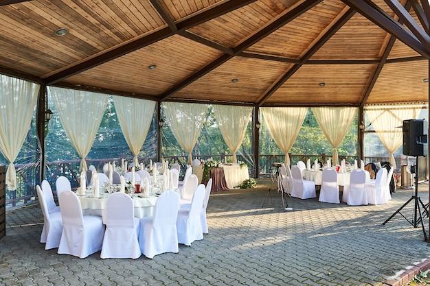 De stoelen en de rondetafel voor gasten worden geserveerd met bestek, bloemen en serviesgoed en afgedekt met een tafelkleed